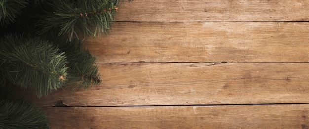 Houten achtergrond met takken van een kerstboom. concept voor kerstmis en nieuwjaar. banier. plat lag, bovenaanzicht.