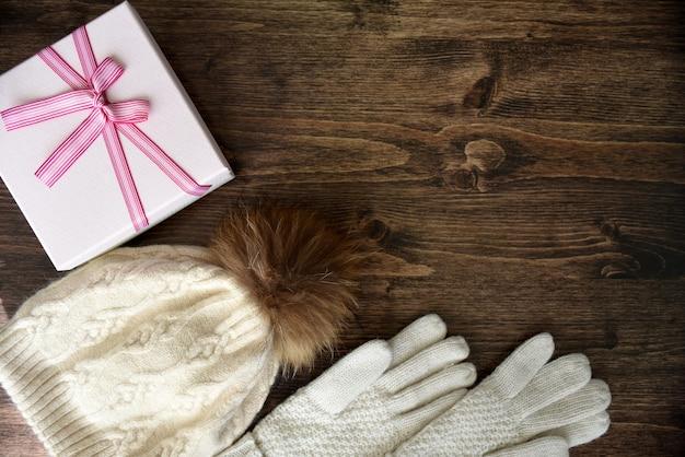 Houten achtergrond met warme muts met pom pom, handschoenen en geschenkdoos