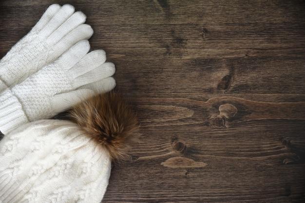 Houten achtergrond met warme witte handschoenen en muts met pom pom