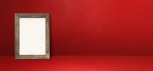 Houten afbeeldingsframe leunend op een rode muur. lege mockup-sjabloon. horizontale banner