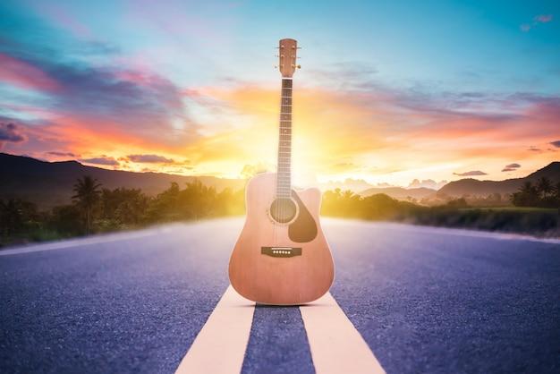 Houten akoestische gitaar die op straat met zonsopgangachtergrond liggen, reis van musicusconcept