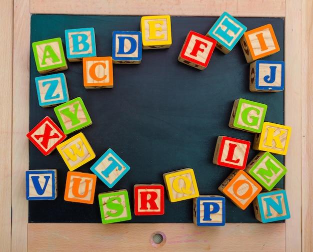 Houten alfabet blokken met letters op een houten bord