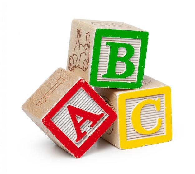 Houten alfabetblokken die op witte achtergrond worden geïsoleerd