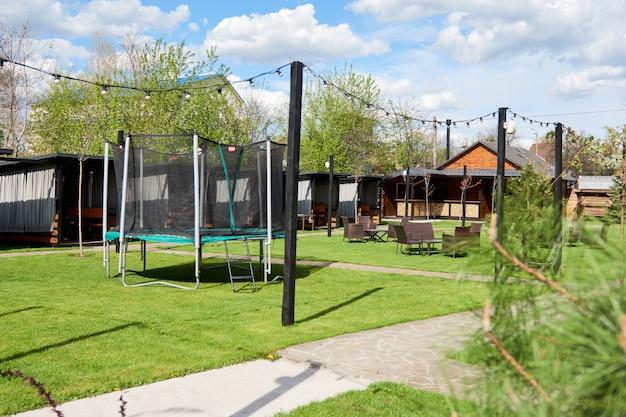 Houten alkoofgazebo in de golfclub van het buitenwijkenplatteland. de plek voor vrije tijd longe, ligstoelen. soorten op de speelplaats springen en springen op de trampoline in de achtertuin
