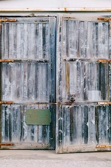 Houten antieke deur met groene patch en metalen sluitingen