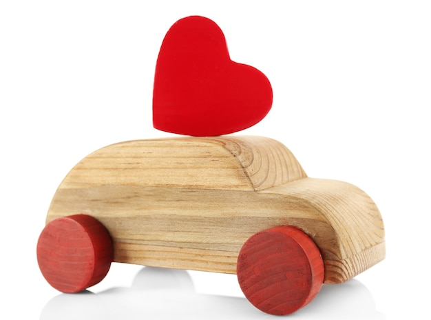 Houten auto met een klein rood hartcijfer dat op wit wordt geïsoleerd