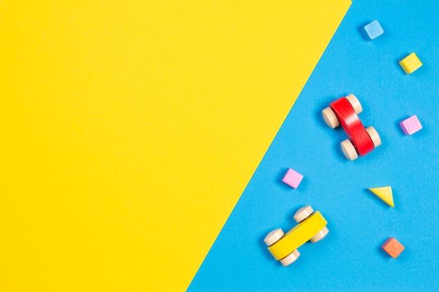 Houten autospeelgoed en kleurrijke kubussen op lichtblauwe en gele achtergrond