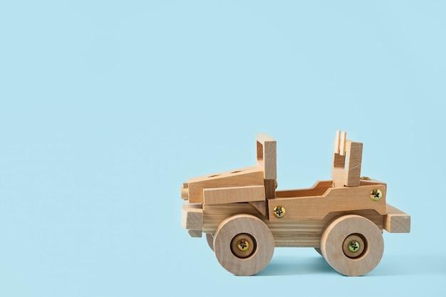 Houten autostuk speelgoed op blauwe achtergrond met exemplaarruimte voor tekst