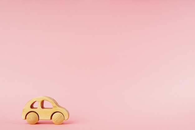 Houten babyauto op een roze pastelkleurachtergrond met copyspace.