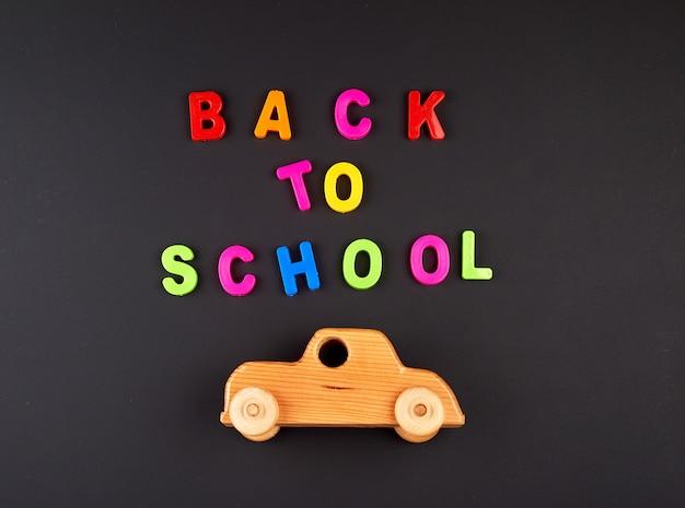 Houten babyauto op zwart schoolbord, concept terug naar school