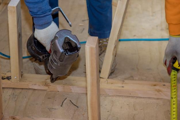 Houten balkconstructie op luchtspijkerpistool pneumatisch spijkermachine in de nieuwe woningbouw