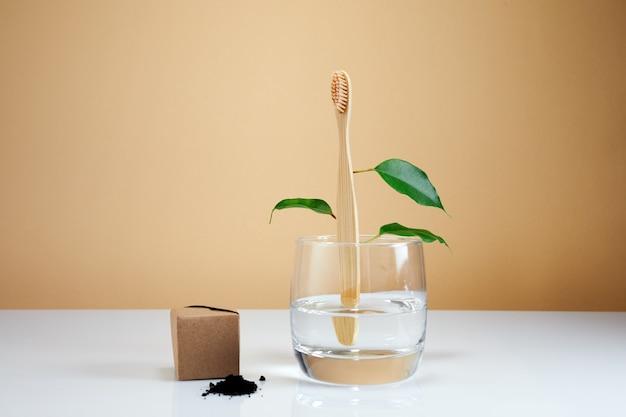 Houten bamboe tandenborstel met bladeren en zwarte houtskooltandpasta. natuurlijk schoonheidsproduct voor de badkamer.