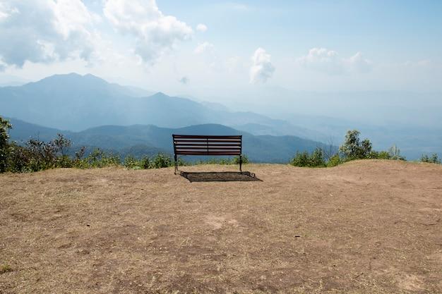 Houten bank buiten landschap met uitzicht op de bergen.