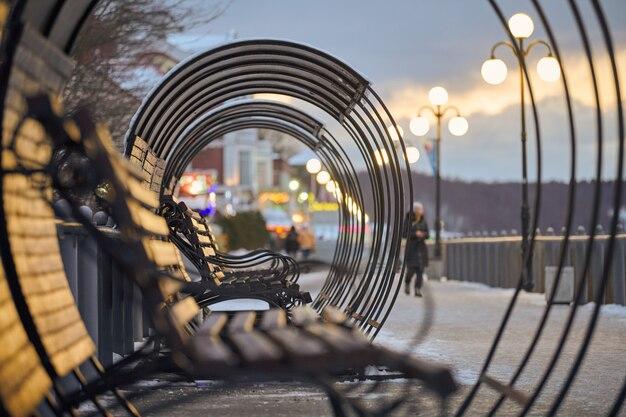 Houten banken in lantaarnlicht in stadspark. mensen lopen door steegjes. avond winterlandschap.