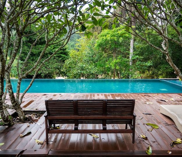Houten bankje in huis bij het zwembad met een warme tropische jungleregen die valt in thailand.