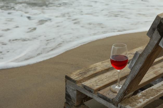 Houten bankje met glas wijn op zandstrand aan zee