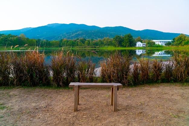 Houten bankje met prachtig meer in chiang mai met beboste berg en twilight hemel in thailand.