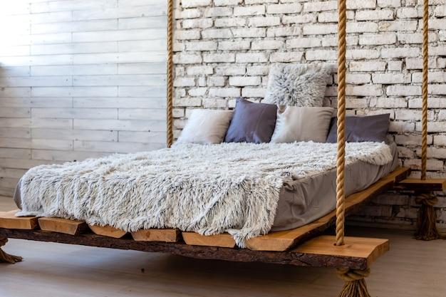Houten bed met kussens en een bontdeken die aan de touwen hangt