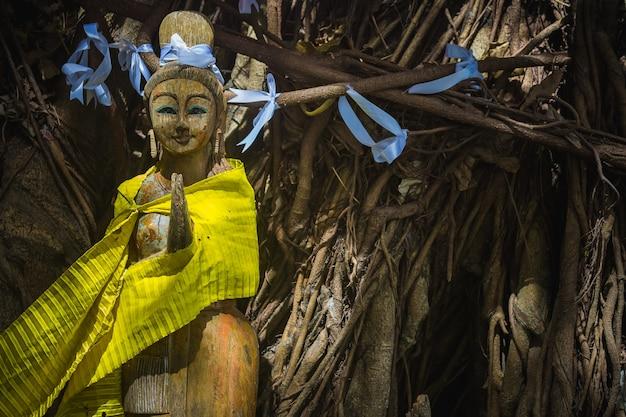 Houten beeld van bidden of meditatie geest van bomen meisje boom met linten thaise groet wai