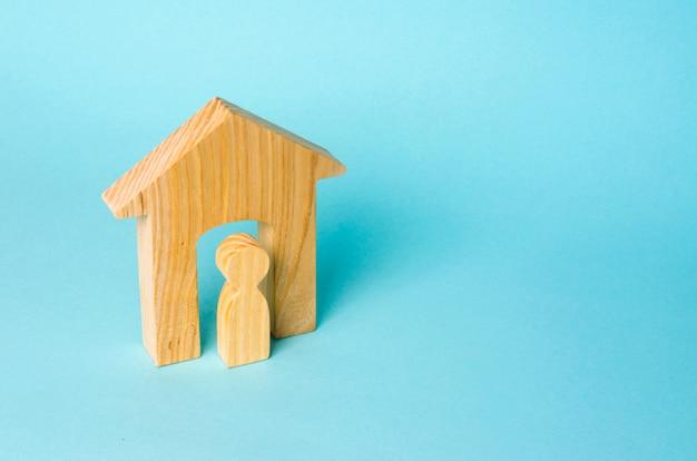 Houten beeldje van een man in een huis op een blauwe achtergrond