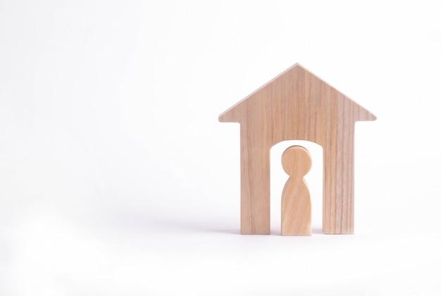 Houten beeldje van een man in een huis op een witte achtergrond