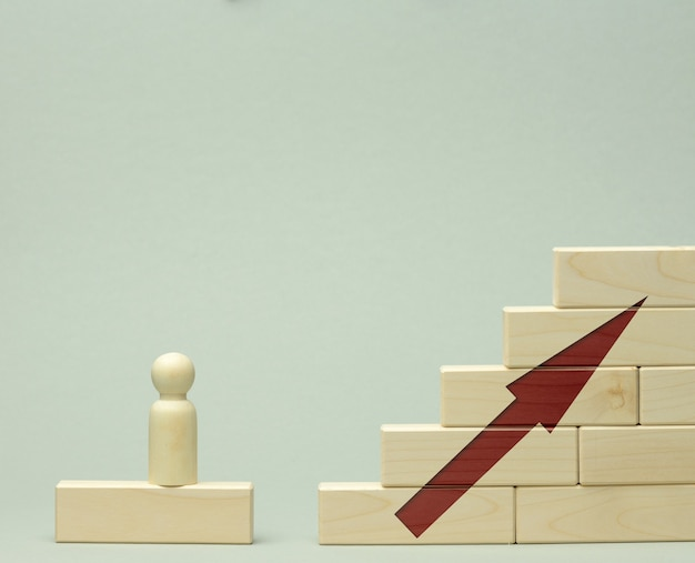 Houten beeldje van een man staat op een trap gemaakt van blokken op de eerste trede