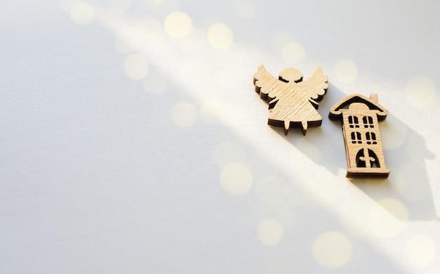 Houten beeldjes in de vorm van een huis en een engel op een witte achtergrond