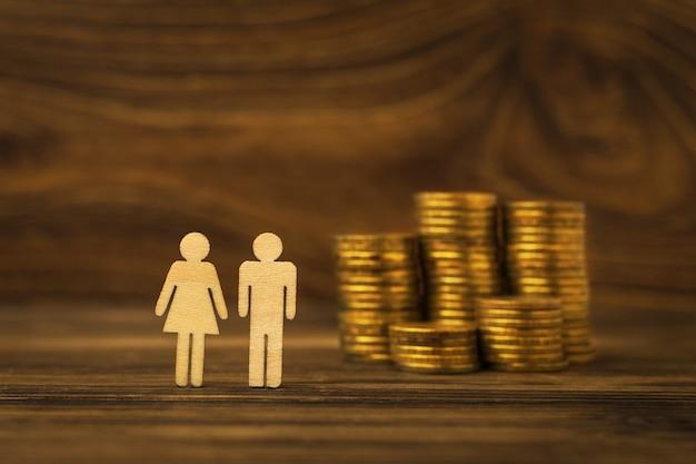 Houten beeldjes van een man en een vrouw en een stapel metalen munten op een houten ondergrond. het concept van gezinsbudget en besparingen.