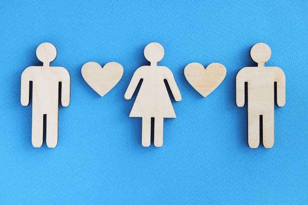 Houten beeldjes van mannen en vrouwen met hartjes op blauwe achtergrond
