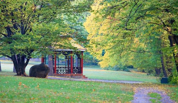 Houten belvedère, groot stenen en voetpad in herfst stadspark