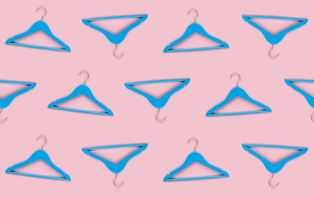 Houten blauwe hanger met zwart papieren label geïsoleerd op roze papieren achtergrond. naadloos patroonmodel