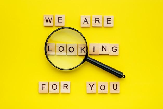 Houten blok belettering we zijn op zoek naar jou en vergrootglas op gele achtergrond.