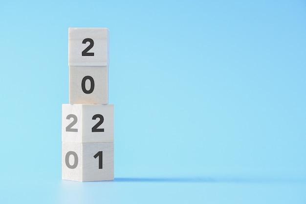 Houten blok dat verandert van nieuwjaar 2020 naar 2021 op geïsoleerde achtergrond