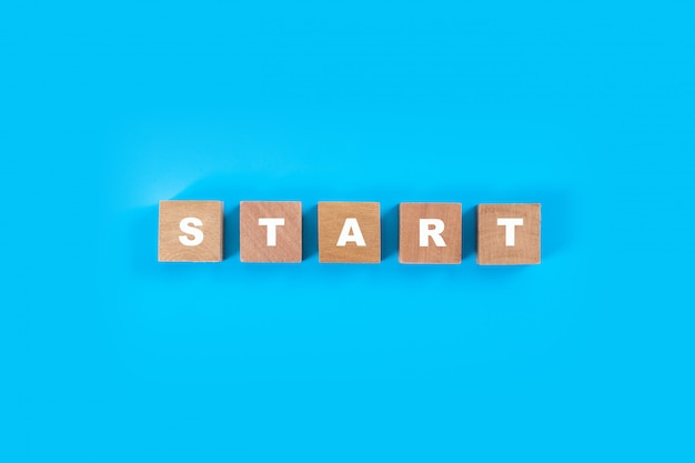 Houten blok kubussen voor het formuleren van start op blauwe achtergrond