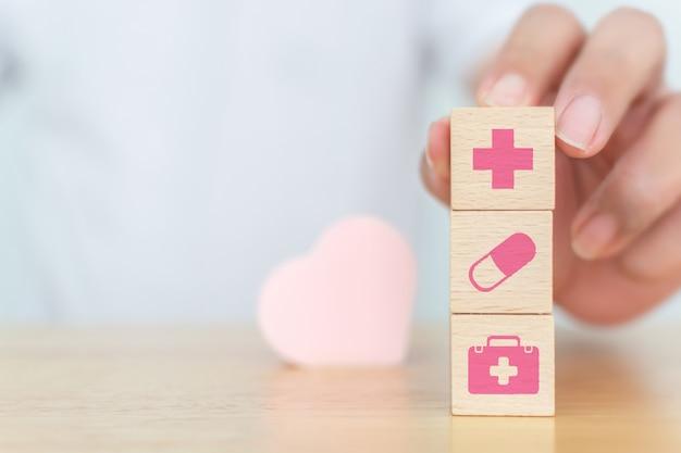 Houten blok kubusvorm op houten tafel met pictogram gezondheidszorg
