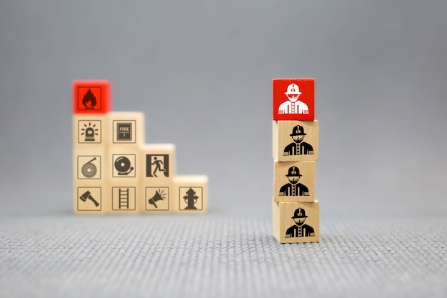 Houten blok met brandweerman pictogram voor vuur en veiligheid.