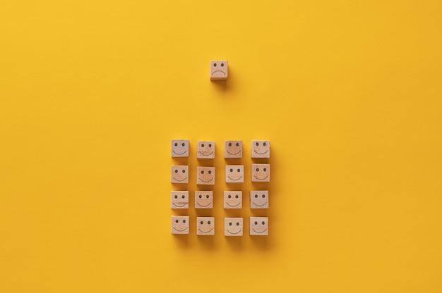 Houten blok met een droevig gezicht boven een groep van hen met een blij gezicht erop in een conceptueel beeld.