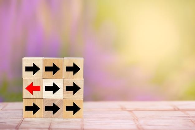 Houten blok rode pijl wijst de andere kant storend van de zwarte pijlen op houten tafel.