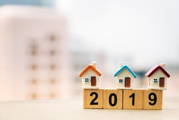 Houten blok woord 2019 nieuw jaar en huis op stapel munten stapel.