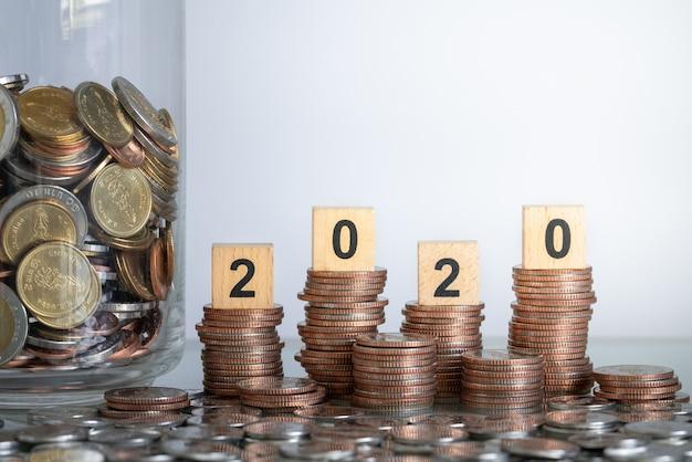 Houten blokaantal jaar 2020 op muntstukstapels met stapel van muntstukken in glaskruik voor zaken en besparingenconcept.