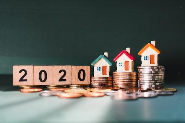 Houten blokjaar 2020 en minihuis op stapelmuntstukken die als bedrijfs financieel en bezit onroerende goederenconcept gebruiken