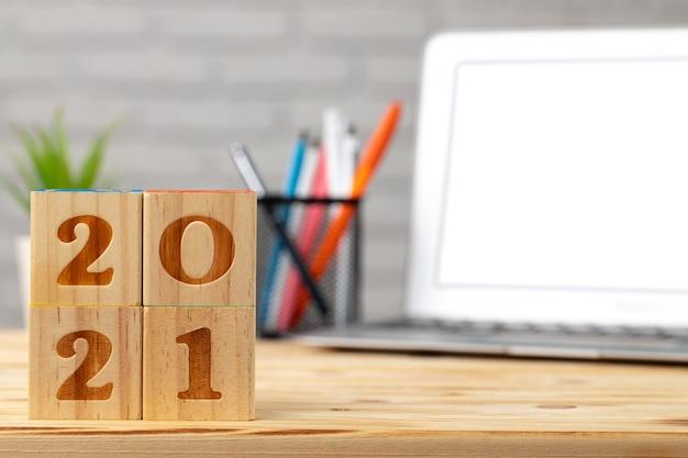Houten blokjes 2021 jaar op werktafel met opengeklapte laptop. concept van 2021