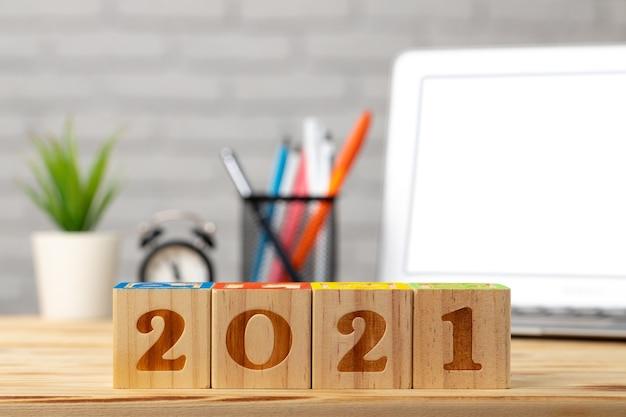 Houten blokjes 2021 jaar op werktafel met opengeklapte laptop.