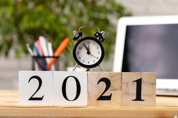 Houten blokjes 2021 jaar op werktafel met opengeklapte laptop