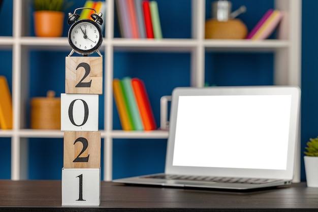 Houten blokjes 2021 op werktafel met opengeklapte laptop