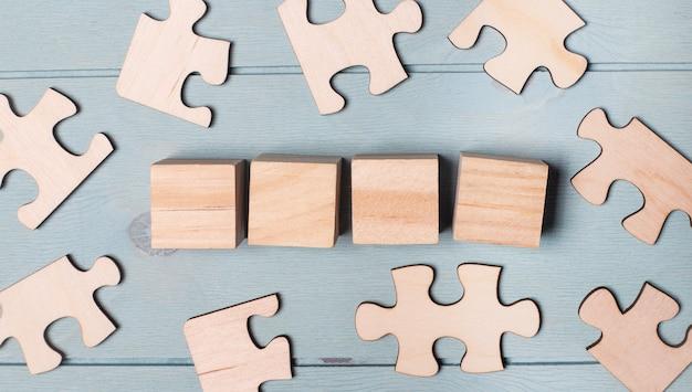 Houten blokjes en blanco puzzels liggen op een blauwe achtergrond. sjabloon. kopieer ruimte