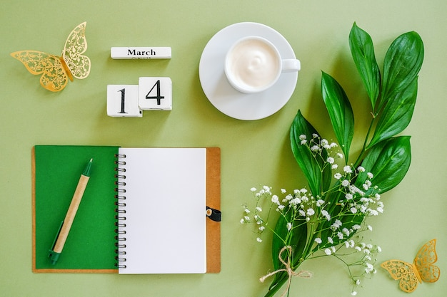 Houten blokjes kalender 14 maart. kladblok, kopje koffie, boeket bloemen op groene achtergrond. concept hallo lente bovenaanzicht plat lag mock up