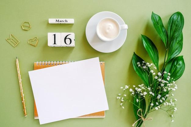 Houten blokjes kalender 16 maart. kladblok, kopje koffie, boeket bloemen op groene achtergrond. concept hallo lente