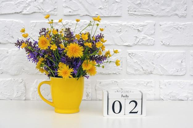 Houten blokjes kalender 2 juli en gele beker met felgekleurde bloemen tegen witte bakstenen muur.