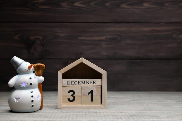 Houten blokjes met de cijfers 31 december en een gloeiende sneeuwpop.